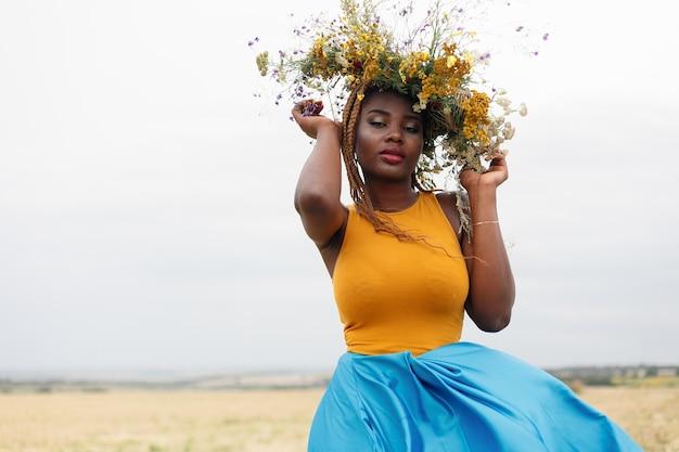 Retrato de uma jovem mulher afro-americana, modelo da moda, com grandes flores no cabelo. retrato de uma menina em um plano torto em um campo com flores. coroa na cabeça dela