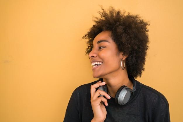 Retrato de uma jovem mulher afro-americana, parecendo confiante e usando fones de ouvido pretos sobre fundo amarelo.