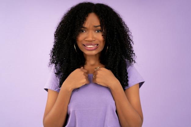 Retrato de uma jovem mulher afro com expressão chocada em pé contra um fundo isolado.