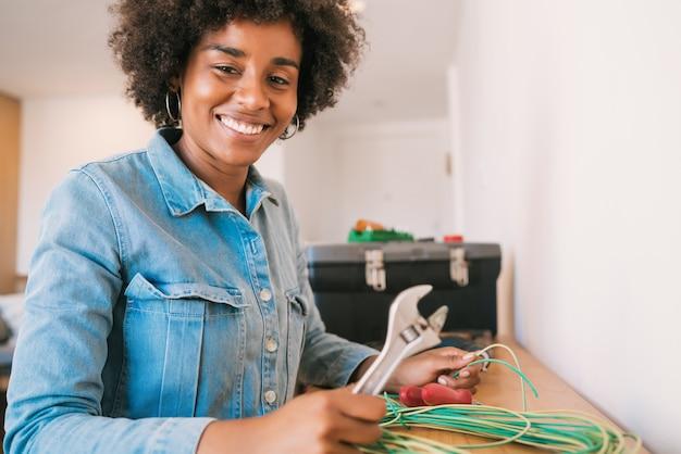Retrato de uma jovem mulher afro, consertando o problema de eletricidade com cabos na nova casa. conceito de casa de reparo e renovação.