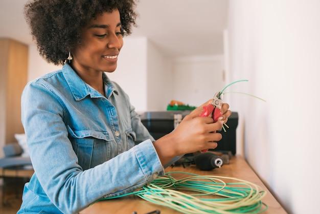 Retrato de uma jovem mulher afro, corrigindo o problema de eletricidade com cabos na nova casa. conceito de casa de reparo e renovação.