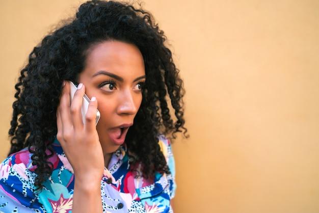 Retrato de uma jovem mulher afro, falando ao telefone com uma expressão chocada contra um fundo amarelo. conceito de comunicação.