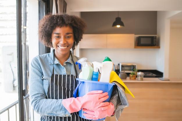 Retrato de uma jovem mulher afro, segurando um balde com produtos de limpeza em casa. conceito de arrumação e limpeza.