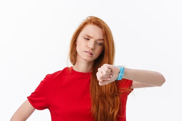Retrato de uma jovem mulher, apontando o dedo no relógio de pulso, isolado no branco