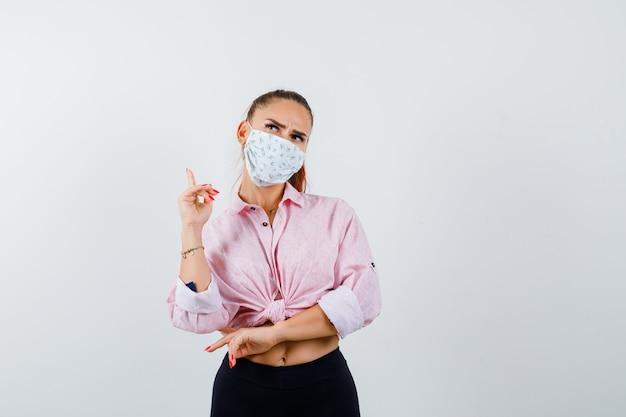Retrato de uma jovem mulher apontando para cima com camisa, calça, máscara médica e olhando pensativa para a frente