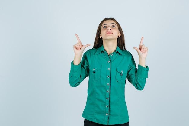 Retrato de uma jovem mulher apontando para cima com uma camisa verde e olhando esperançosa de frente