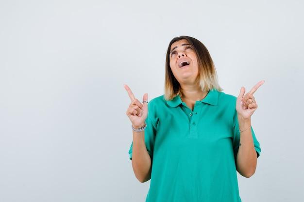 Retrato de uma jovem mulher apontando para cima, olhando para cima em uma camiseta pólo e olhando confusa para a frente