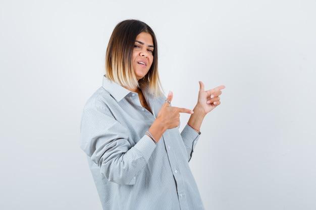 Retrato de uma jovem mulher apontando para o lado direito com uma camisa grande e olhando frontalmente feliz