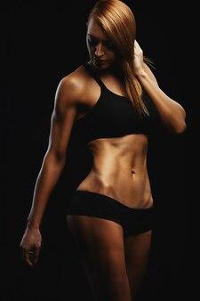 Retrato de uma jovem mulher apta que levanta vestindo um sutiã esportivo contra parede preta. atleta determinado.