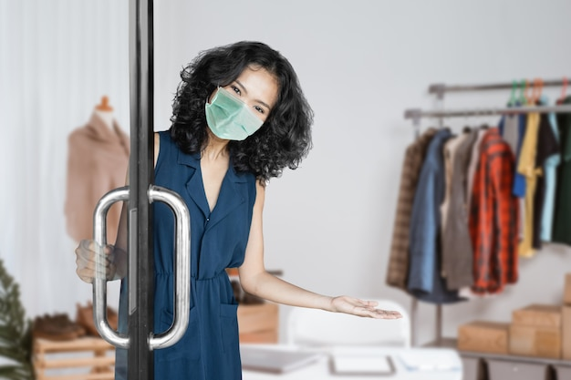 Retrato de uma jovem mulher asiática atraente dando as boas-vindas ao cliente em sua pequena loja durante uma nova máscara facial normal usando