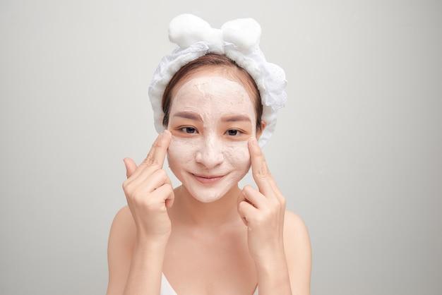 Retrato de uma jovem mulher asiática bonita, aplicando a máscara facial de argila branca.