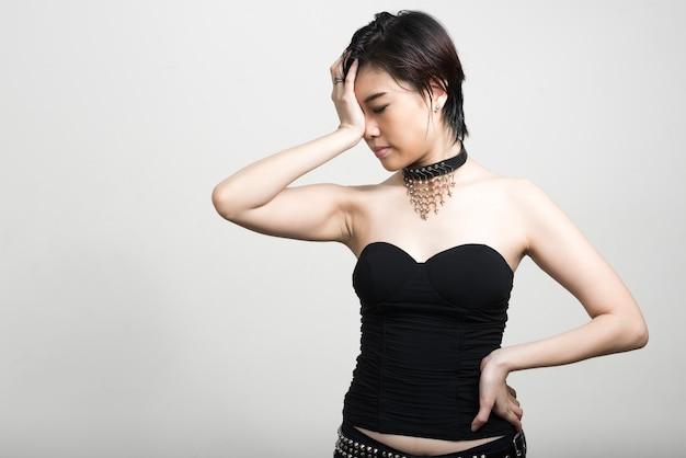 Retrato de uma jovem mulher asiática bonita com cabelo curto contra uma parede branca