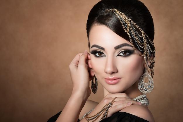 Retrato de uma jovem mulher asiática bonita com maquiagem de noite e acessórios para a cabeça