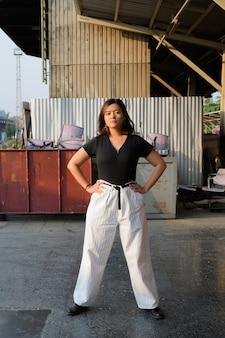 Retrato de uma jovem mulher asiática bonita contra a vista de uma rua urbana