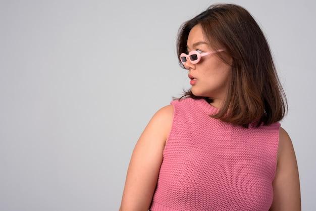 Retrato de uma jovem mulher asiática bonita contra uma parede branca