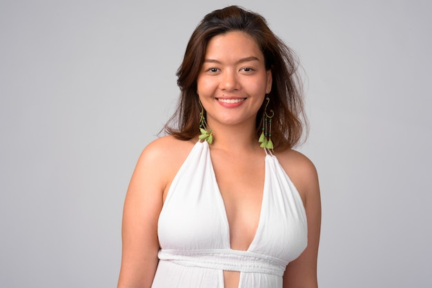 Retrato de uma jovem mulher asiática bonita pronta para o verão contra uma parede branca