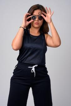 Retrato de uma jovem mulher asiática bonita usando óculos escuros com design de alvo Foto Premium