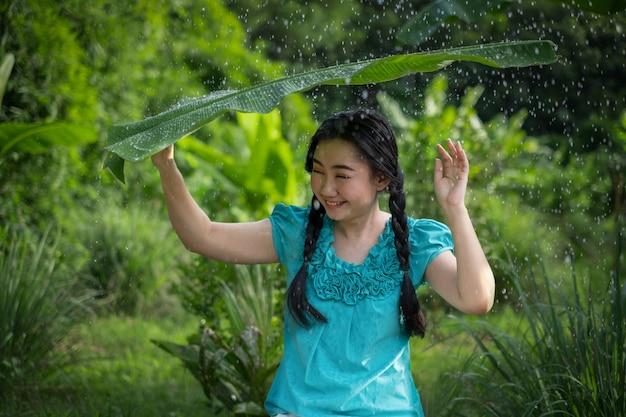 Retrato de uma jovem mulher asiática com cabelos pretos, segurando uma folha de bananeira na chuva no jardim verde