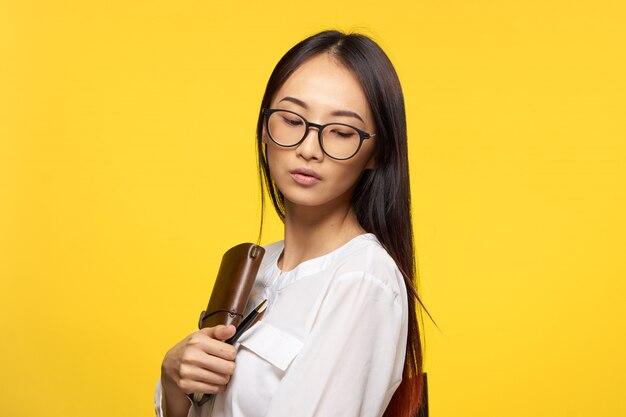 Retrato de uma jovem mulher asiática com óculos e agenda
