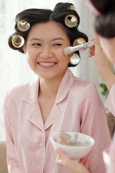 Retrato de uma jovem mulher asiática com rolos de cabelo recebendo máscara de argila aplicada no rosto