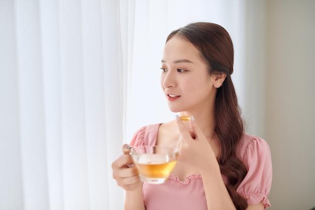 Retrato de uma jovem mulher asiática comendo pílula de vitamina para cuidados de saúde em casa.