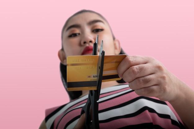 Retrato de uma jovem mulher asiática cortando um cartão de crédito com uma tesoura para parar de gastar em compras no rosa