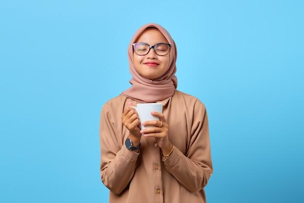 Retrato de uma jovem mulher asiática feliz segurando uma caneca sobre um fundo azul
