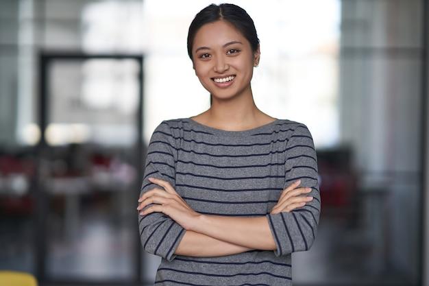 Retrato de uma jovem mulher asiática feliz trabalhadora de escritório em roupas casuais, de braços cruzados