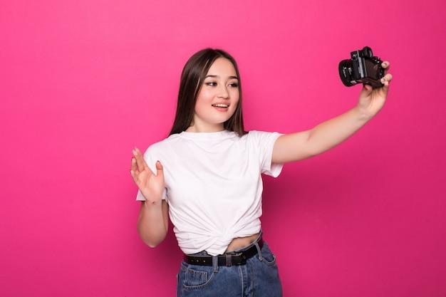 Retrato de uma jovem mulher asiática feliz vestida de vestido branco e chapéu de verão segurando a câmera fotográfica e olhando para o espaço da cópia sobre parede rosa