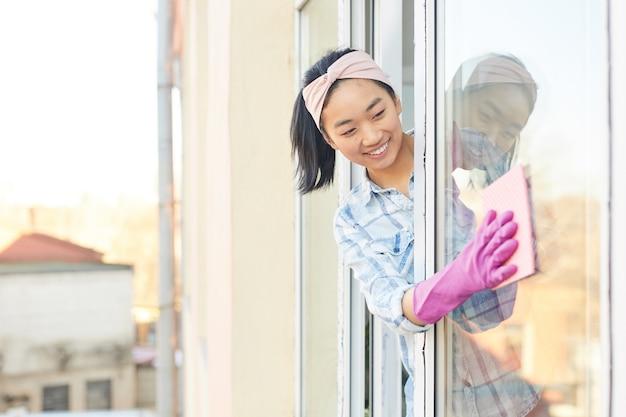Retrato de uma jovem mulher asiática lavando janelas e sorrindo feliz enquanto desfruta da limpeza da primavera, filmado de fora