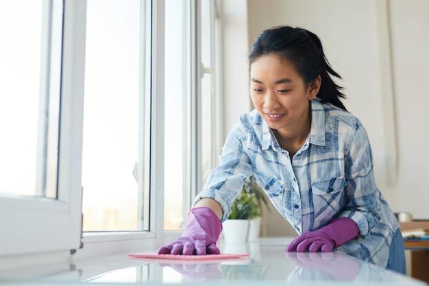 Retrato de uma jovem mulher asiática lavando janelas e sorrindo feliz enquanto desfruta da limpeza da primavera