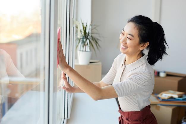 Retrato de uma jovem mulher asiática lavando janelas enquanto faz a limpeza da primavera em casa ou apartamento