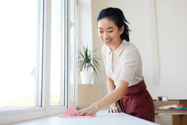 Retrato de uma jovem mulher asiática limpando o parapeito da janela enquanto faz uma faxina na casa ou apartamento