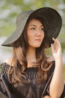 Retrato de uma jovem mulher asiática linda em um levantamento de chapéu. mulher asiática usando chapéu preto.