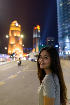 Retrato de uma jovem mulher asiática linda vagando pelas ruas da cidade à noite em kuala lumpur, malásia