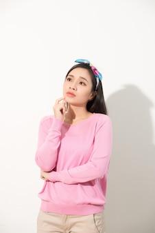 Retrato de uma jovem mulher asiática pensativa, olhando para cima com a mão no queixo isolado