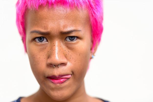Retrato de uma jovem mulher asiática rebelde com cabelo rosa contra o espaço em branco