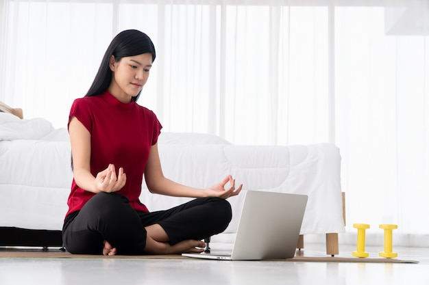 Retrato de uma jovem mulher asiática saudável praticando exercícios de ioga sentado no quarto e aprendendo on-line no laptop em casa. conceito de exercício e relaxamento, tecnologia para um novo estilo de vida normal