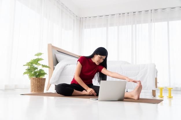 Retrato de uma jovem mulher asiática saudável praticando exercícios de ioga sentado no quarto e aprendendo on-line no laptop em casa.
