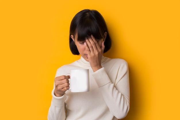 Retrato de uma jovem mulher asiática segurando a cabeça pensando em algo