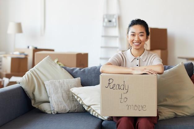 Retrato de uma jovem mulher asiática segurando uma caixa de papelão com inscrição pronta para mover e sorrindo olhando