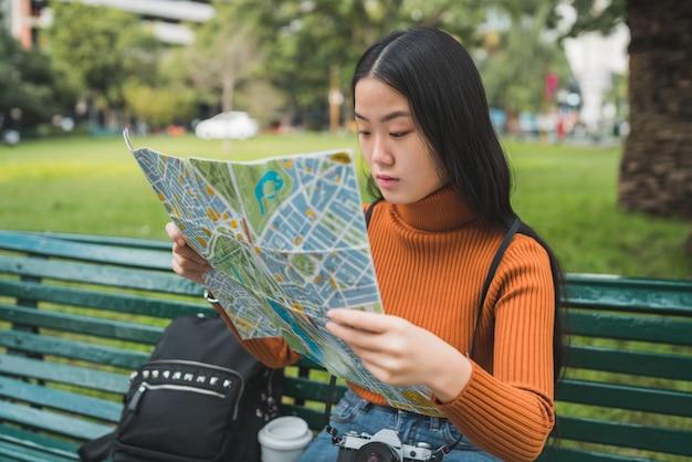Retrato de uma jovem mulher asiática sentada no banco do parque e olhando para um mapa