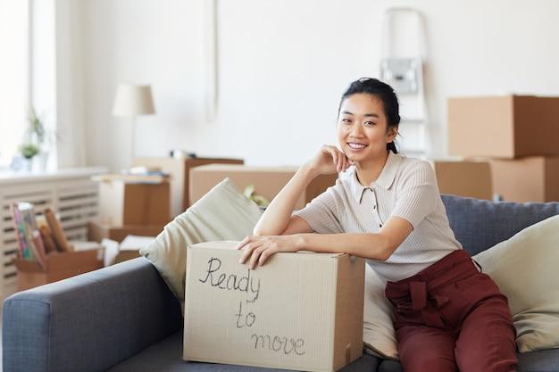 Retrato de uma jovem mulher asiática sorrindo enquanto se inclina sobre uma caixa de papelão com a inscrição pronta para mover