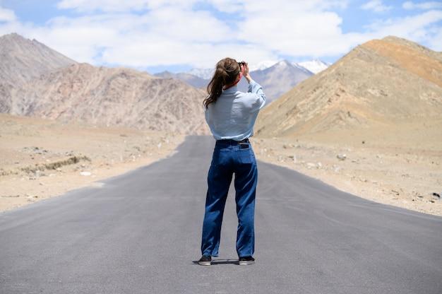 Retrato de uma jovem mulher asiática tirando fotos na estrada