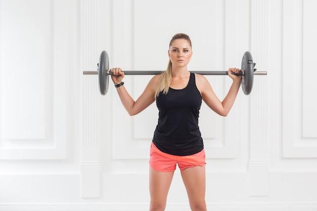 Retrato de uma jovem mulher atlética bonita fisiculturista em shorts rosa e blusa preta, fazendo agachamentos e se exercitando na academia com a barra na parede branca. interno, foto de estúdio, olhando para a câmera