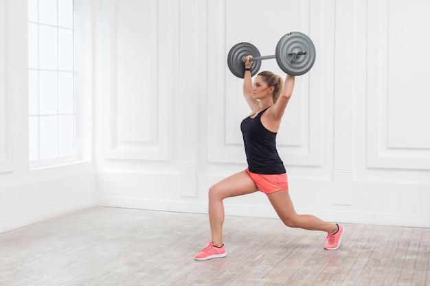 Retrato de uma jovem mulher atlética bonita fisiculturista em shorts rosa e top preto, segurando a barra sobre a cabeça e fazendo agachamentos com uma perna na academia na parede branca. indoor, studio shot