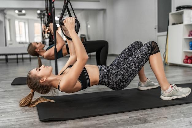 Retrato de uma jovem mulher atlética em roupas esportivas, fazendo exercícios, treinando pernas e glúteos musculosos com cinta de fitness no ginásio