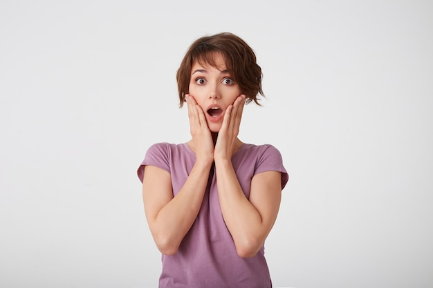 Retrato de uma jovem mulher atraente admirada com uma expressão de surpresa no rosto, em pé sobre uma parede branca com a mariposa bem aberta e os olhos. conceito de emoção positiva.