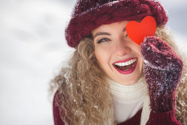 Retrato de uma jovem mulher atraente ao ar livre no inverno, mostrando o coração de papel