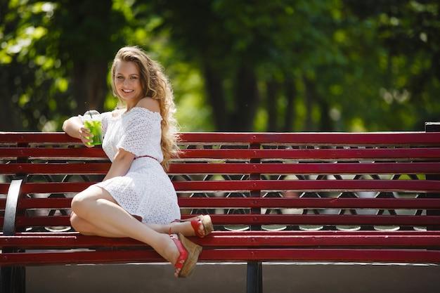 Retrato de uma jovem mulher atraente bonita ao ar livre no verão com um copo de suco gelado ou bebida. menina bonita lá fora com mojito fresco